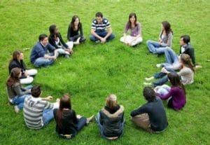 Photo d'un groupe de personnes, assises en cercle, dans l'herbe